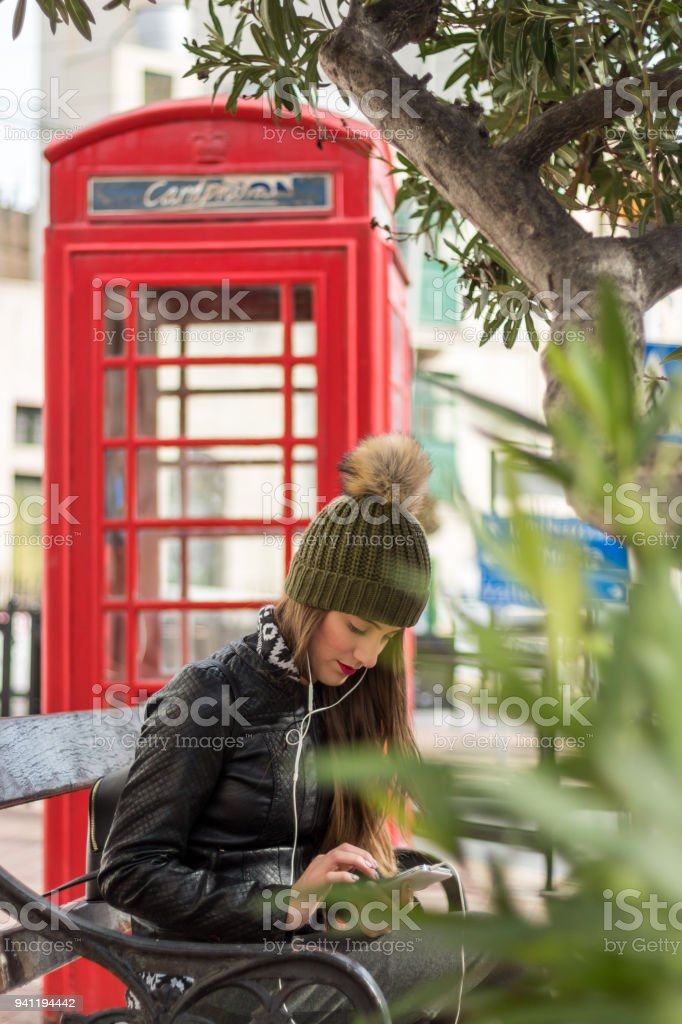 Young girl sitting on a bench and typing message stock photo