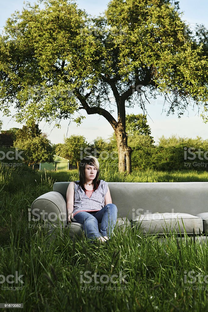 Young Girl Sitting on a Couch Outside royalty-free stock photo