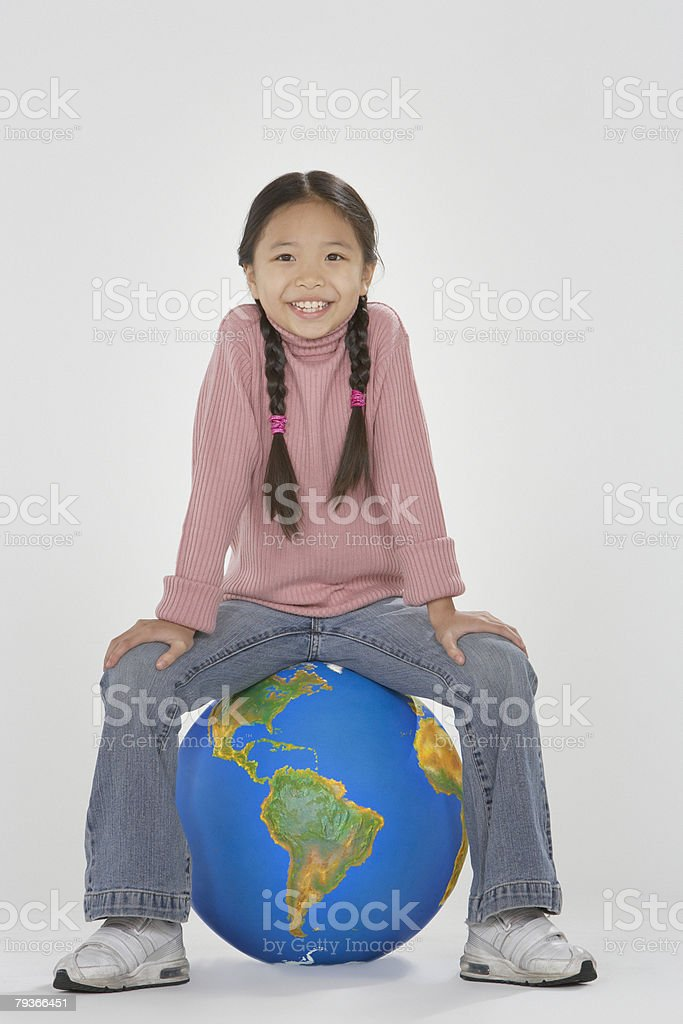 Young girl sitting on a globe indoors royalty-free stock photo
