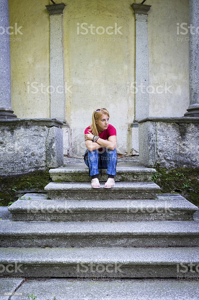 Young girl sitting on a marble staircase. Color image stock photo