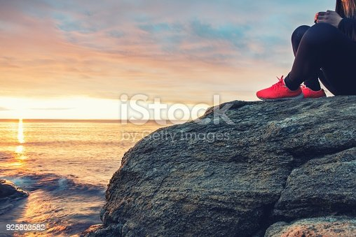 Young girl sitting on a sea rock meeting the morning sun.