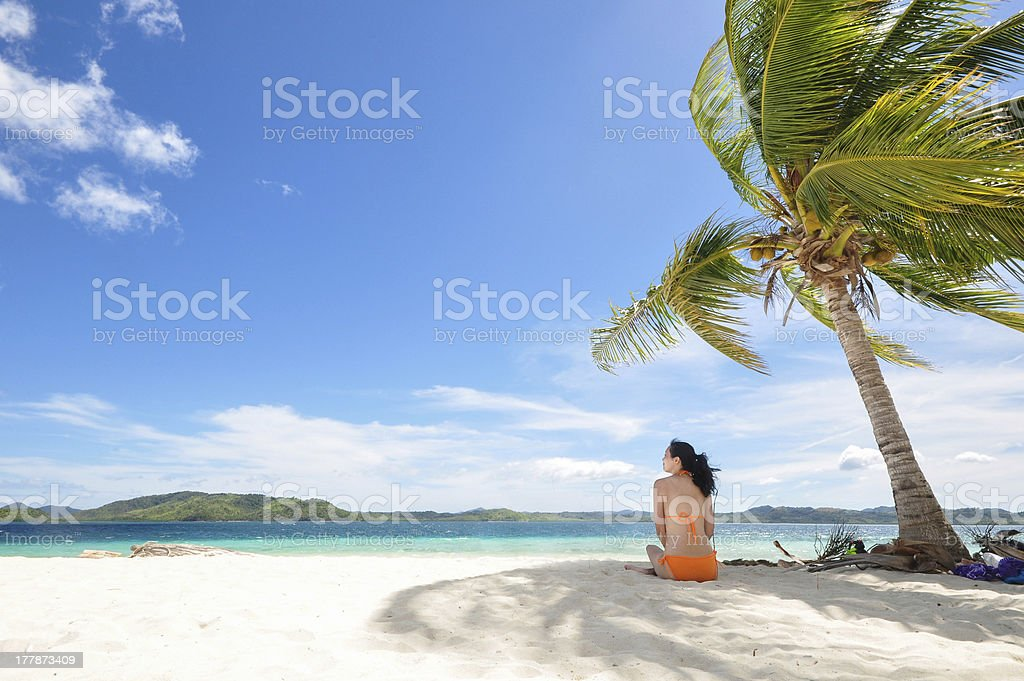 young girl sitting on beach under coconut tree stock photo more