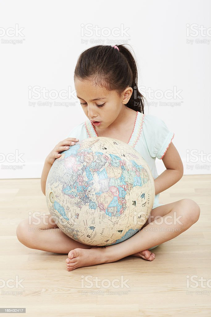 Young girl sitting on floor with globe royalty-free stock photo