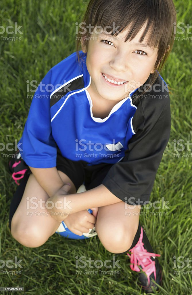 Young girl sitting on her soccer ball royalty-free stock photo