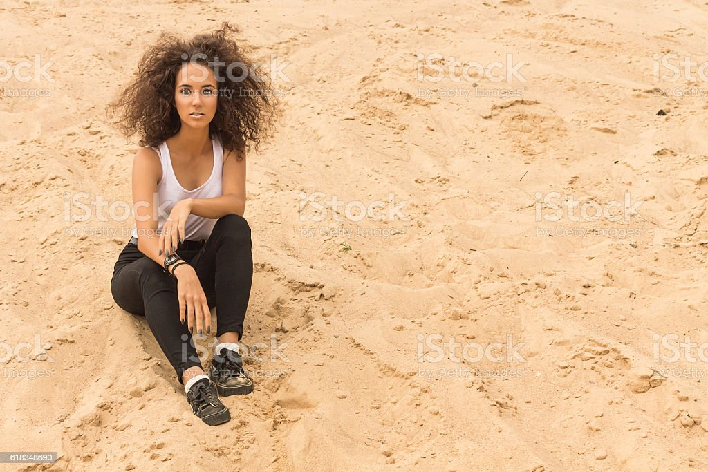 Young Girl Sitting on the Sand. stock photo