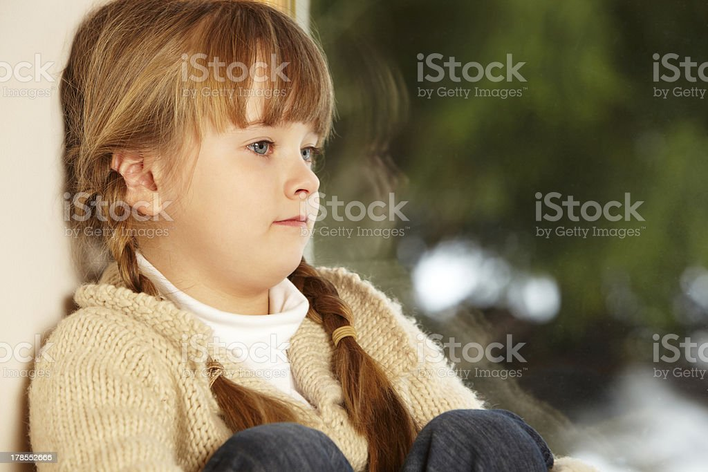 Young Girl Sitting On Window Ledge Looking At Snowy View stock photo