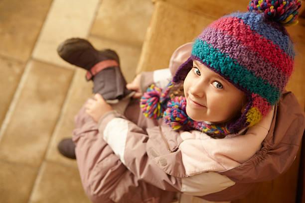 junges mädchen sitzen auf der hölzernen sitz - kinder winterstiefel stock-fotos und bilder