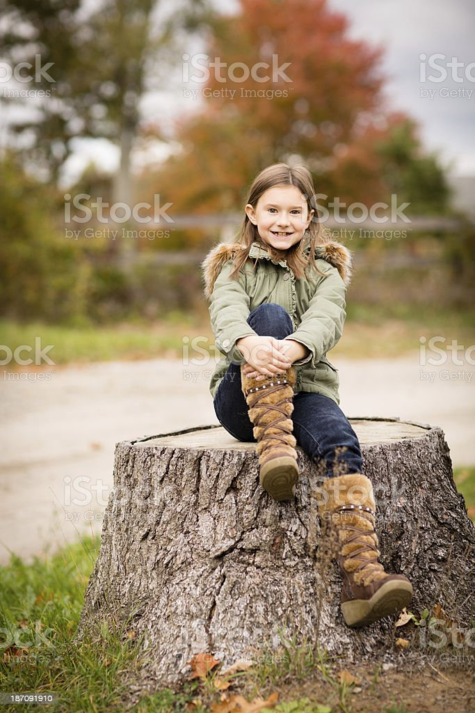 Young Girl Sitting Outside on Tree Stump, in Autumn royalty-free stock photo