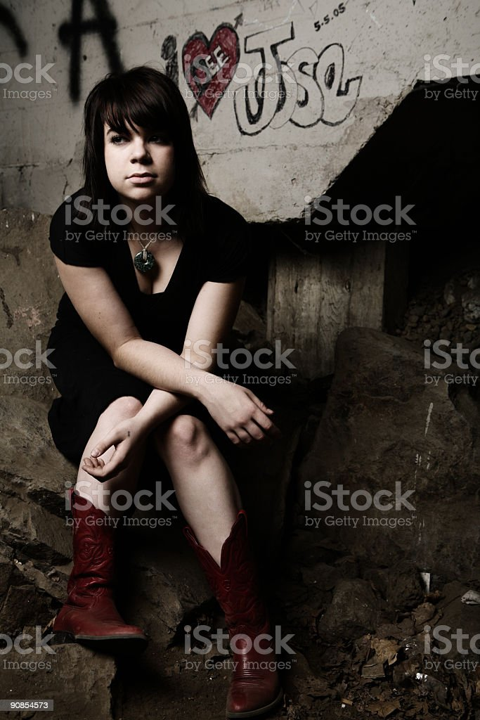 Young Girl Sitting Under a Graffitied Bridge stock photo
