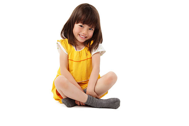 young girl sitting with crossed legs - isolated - sitting on floor stock photos and pictures