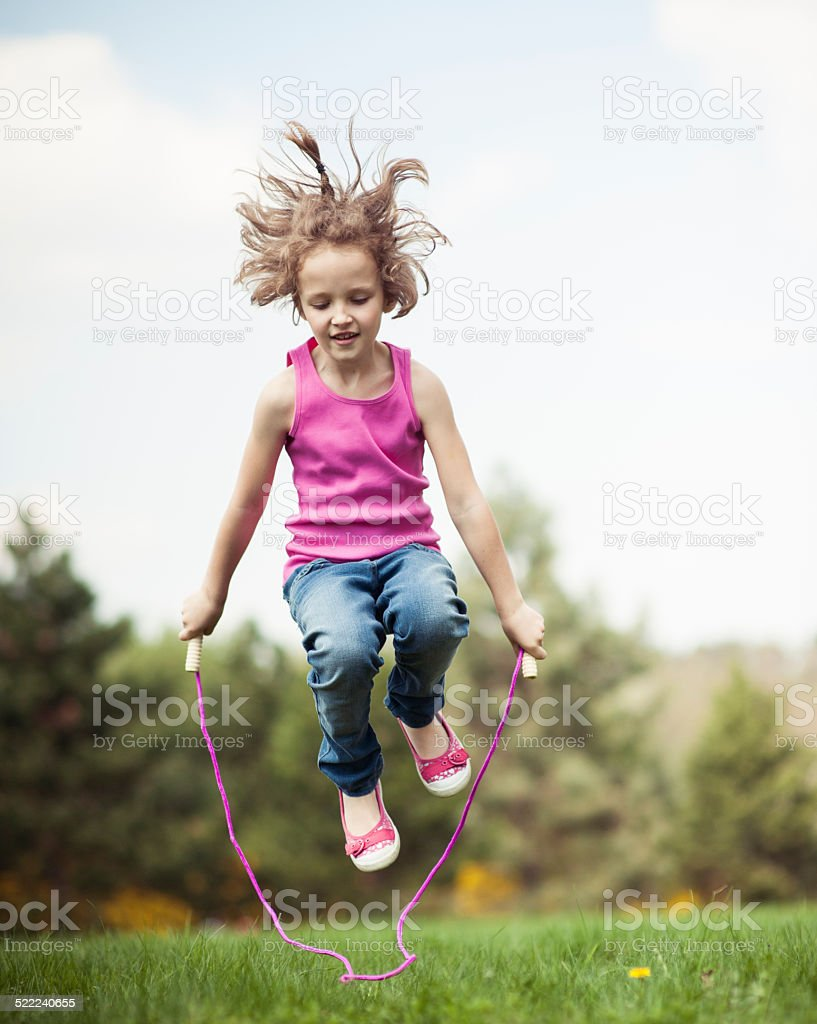 Young girl skipping in park stock photo
