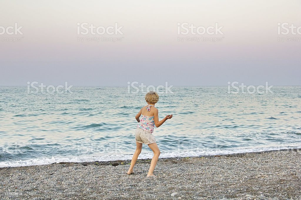 Young Girl Skipping Rocks on Beach stock photo