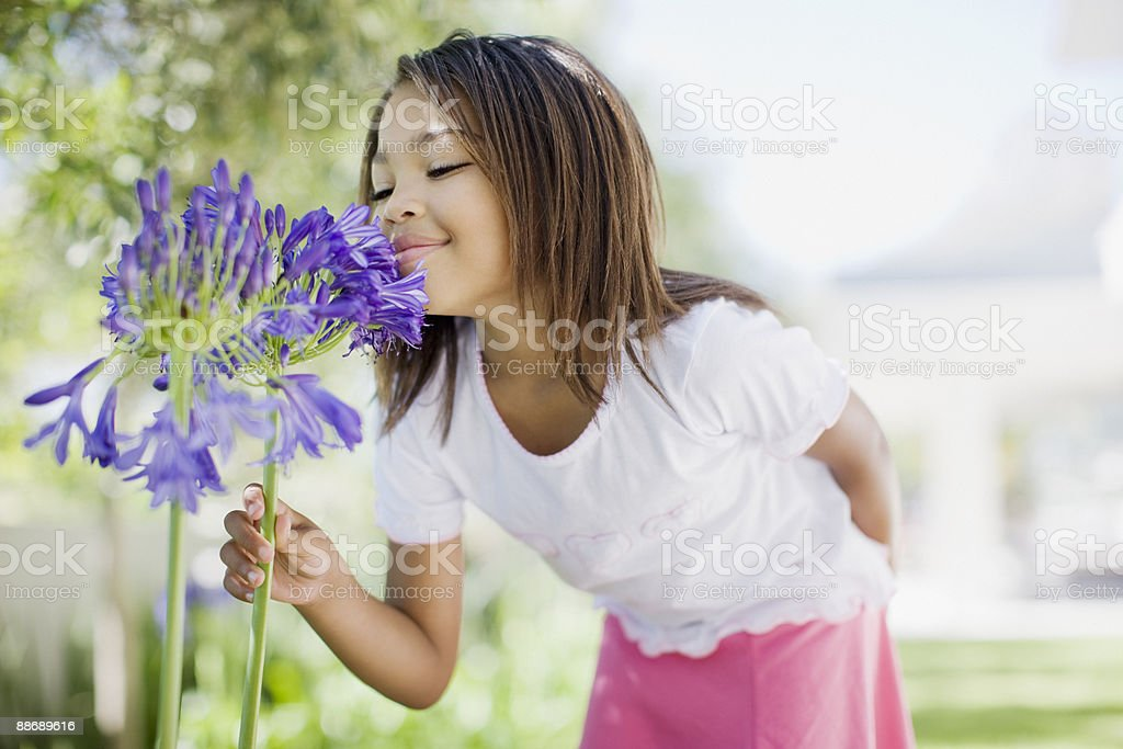 Junges Mädchen riechen Blumen Lizenzfreies stock-foto