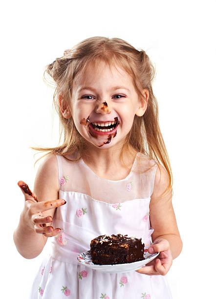 lustige kleine mädchen mit torte - kinderschokolade stock-fotos und bilder