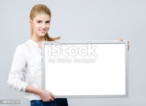 istock Young girl smiling and holding a white blank board. 497512713