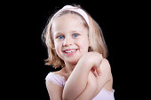 5 Year old blond girl smiling looking straight at the camera