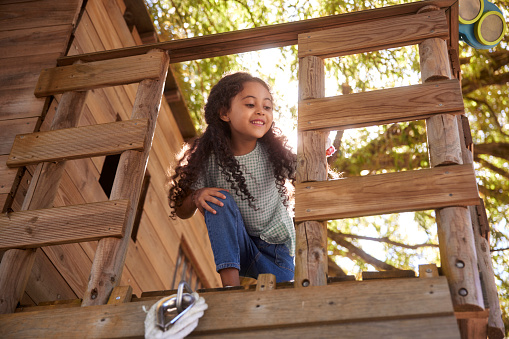 Young little african-american girl with curly hair smiling playing in tree house on summer day
