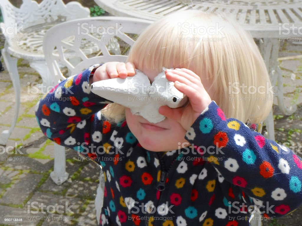 Young girl smiling, pretending recycled egg carton are goggles stock photo