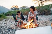 キャンプファイヤーで母親と一緒にマシュマロを焙煎しながら微笑む若い女の子