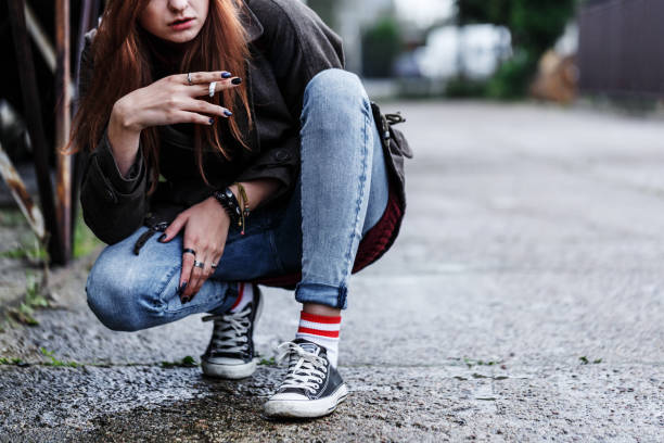 Young girl smoking cigarette Close-up of riotous young girl smoking cigarette on the sidewalk absentee stock pictures, royalty-free photos & images