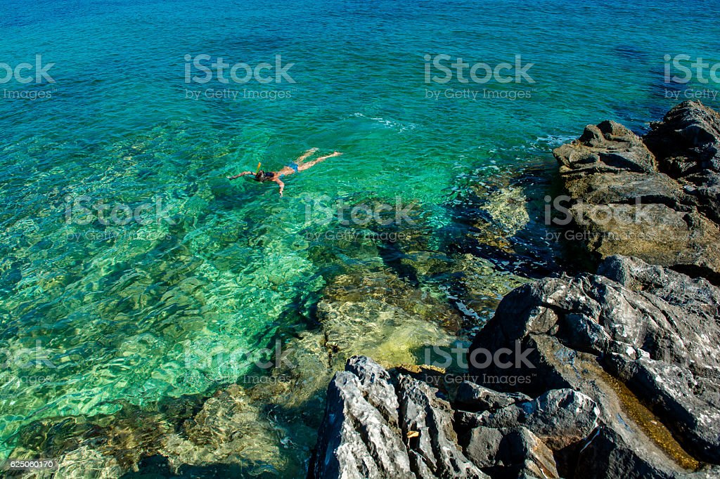 Young Girl Snorkeling through Turquoise Water at the Coast stock photo