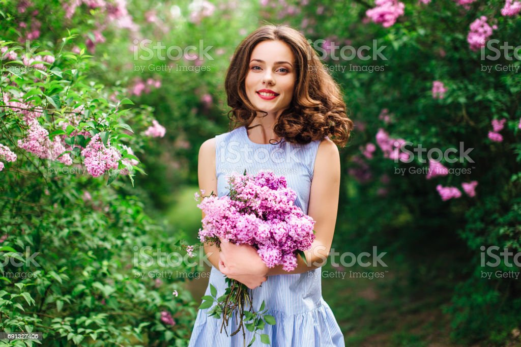 Young girl stand at park background with bouquet of flowers stock photo