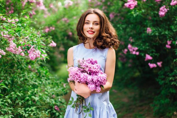 carrinho de menina no fundo do parque com buquê de flores - mulher flores - fotografias e filmes do acervo