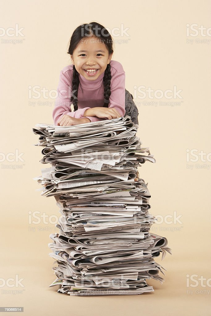 Young girl standing by a stack of newspapers indoors royalty-free stock photo