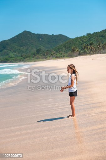 Young caucasian girl standing on a beautiful tropical beach on Lombok Island, Indonesia.