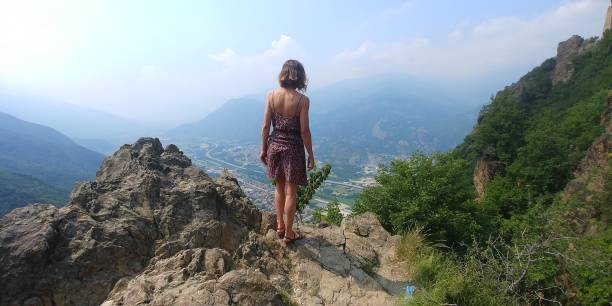 young girl standing on the mountain peak stock photo