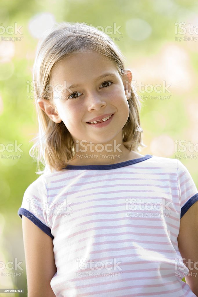 Young girl standing outdoors smiling royalty-free stock photo