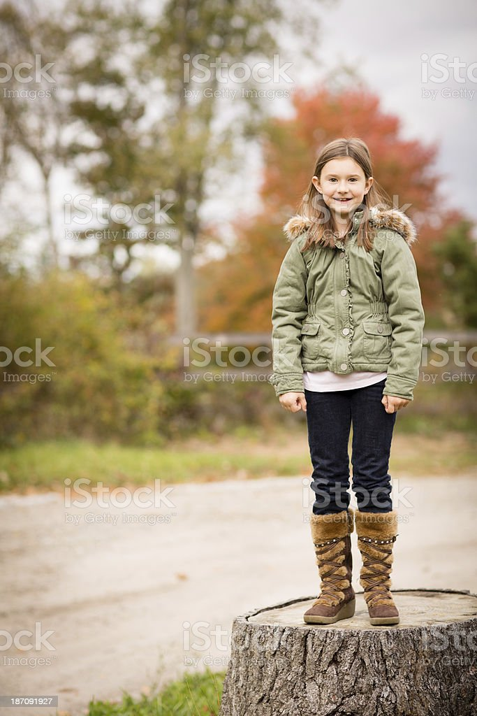 Young Girl Standing Outside on Tree Stump, in Autumn royalty-free stock photo