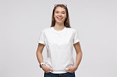 istock Young girl standing with hands in pockets, wearing blank white t-shirt with copy space, isolated on gray background 1153003844