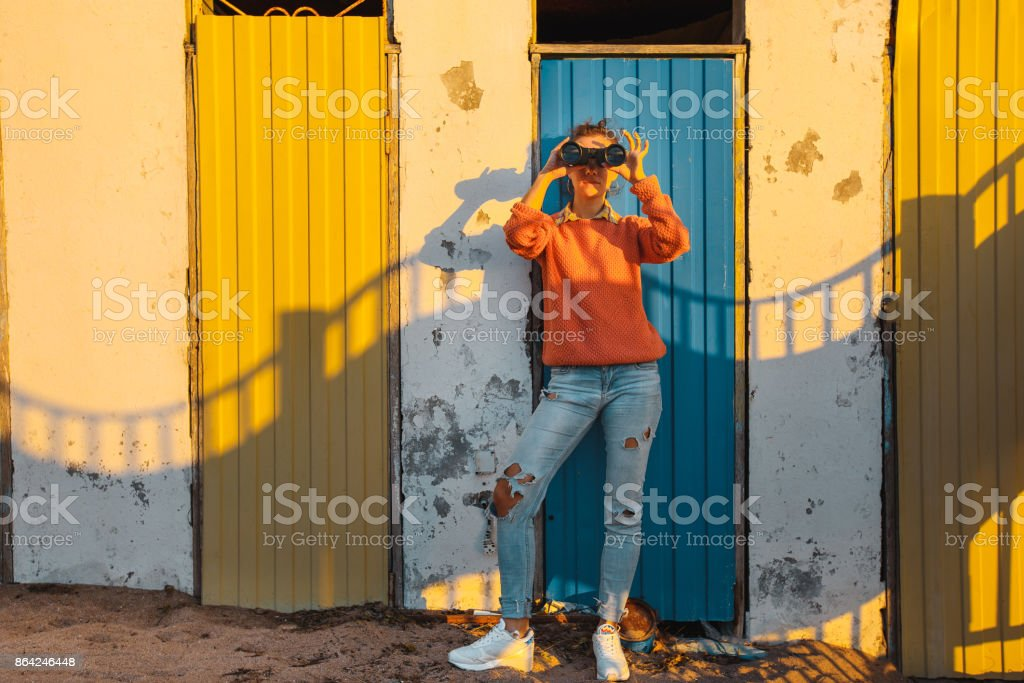 Young Girl Stands Near A Colorful Wall And Looks Through Binoculars royalty-free stock photo
