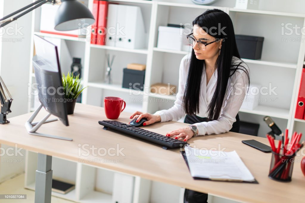 A young girl stands near a table and prints on the keyboard. next to the girl are the documents.
