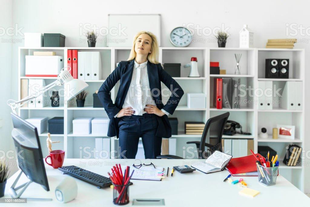 Una joven está parado cerca de una mesa en la oficina, con sus manos en sus caderas. - foto de stock