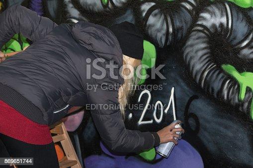 506166130 istock photo Young Girl Street Artist: Spraying on Public Urban City Wall 869651744