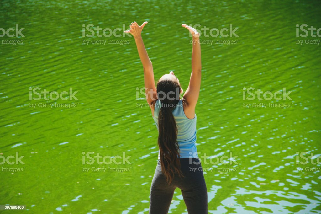 Young girl stretches during training workout exercises outdoor - Stock  image .
