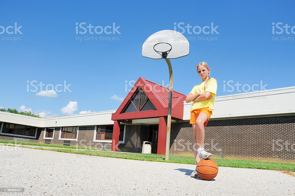 Young Girl Striking a Pose on Schoolyard Playground Basketball Court royalty-free stock photo