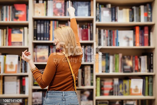 Pretty young girl with loose long blondie hair standing and holding an open book between book shelves in the library, reading and looking into the book