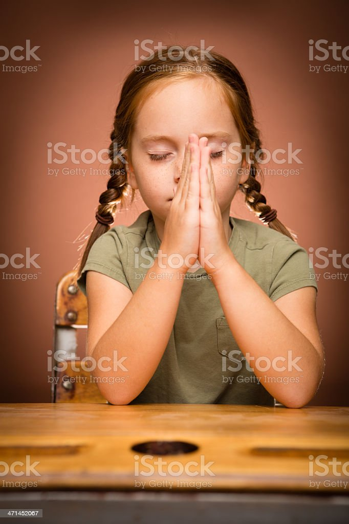 Young Girl Student Praying While Sitting at School Desk royalty-free stock photo