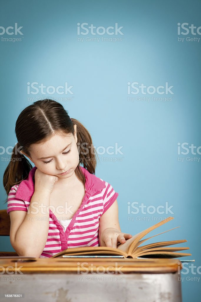 Young Girl Student Reading Book at School Desk royalty-free stock photo