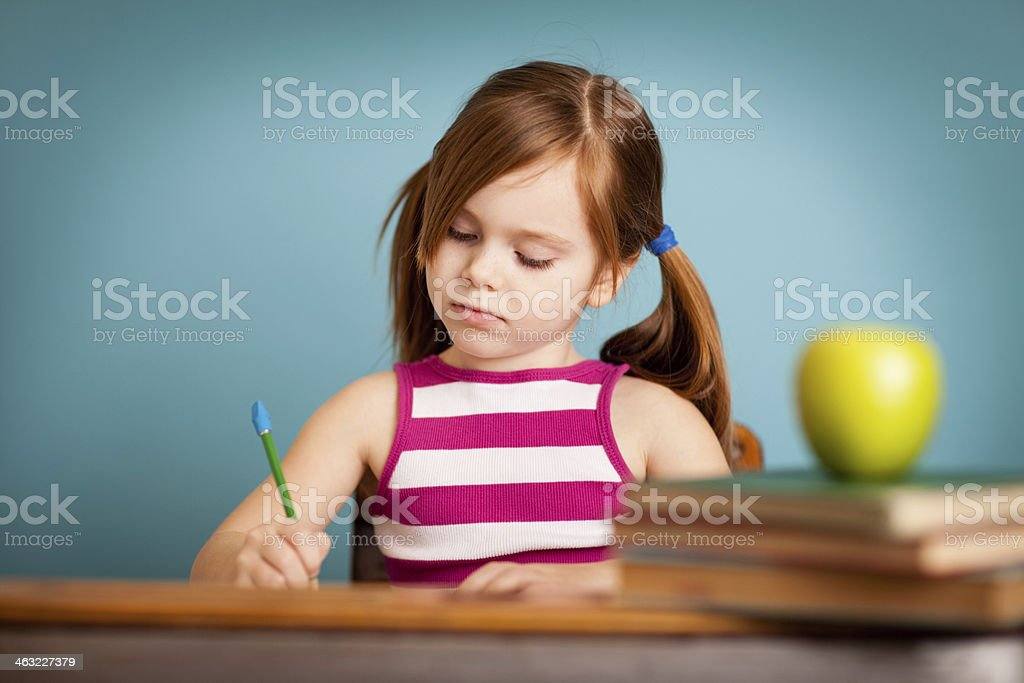 Young Girl Student Sitting at School Desk Doing Her Schoolwork royalty-free stock photo