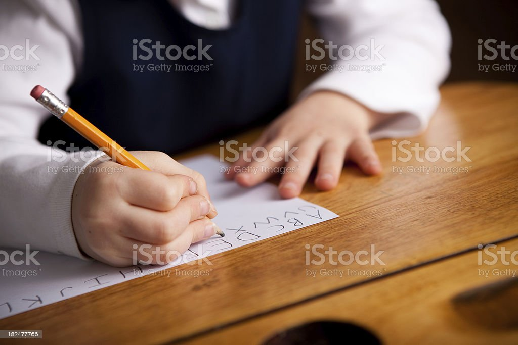 Young Girl Student Sitting in School Desk Writing the Alphabet stock photo