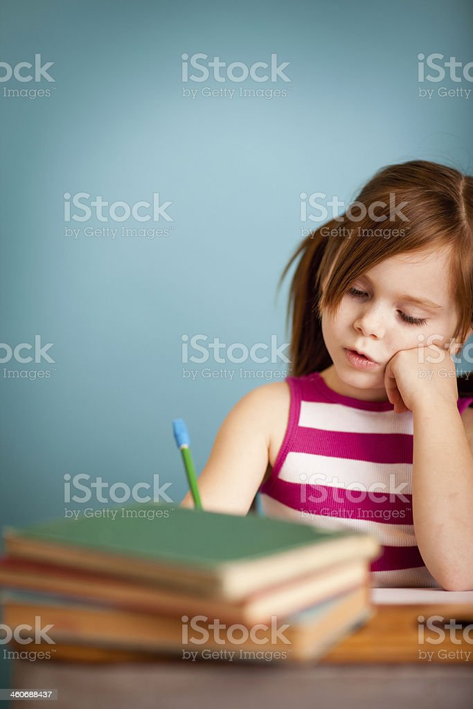 Young Girl Student Working at School Desk, with Copy Space royalty-free stock photo