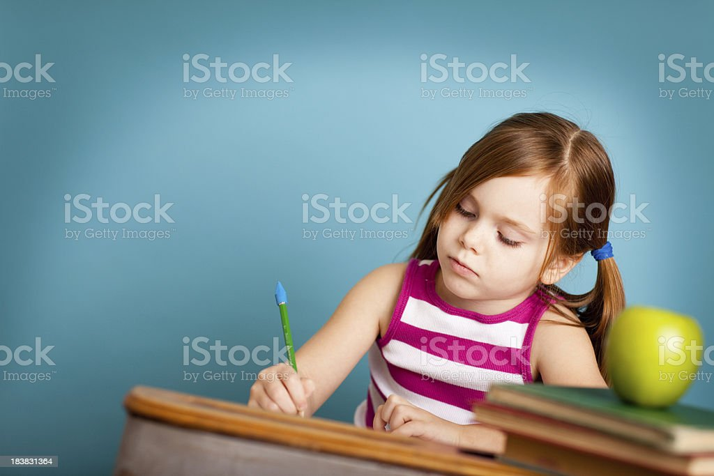 Young Girl Student Writing in School Desk royalty-free stock photo
