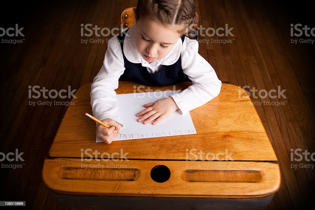 Young Girl Student Writing While Sitting in School Desk stock photo