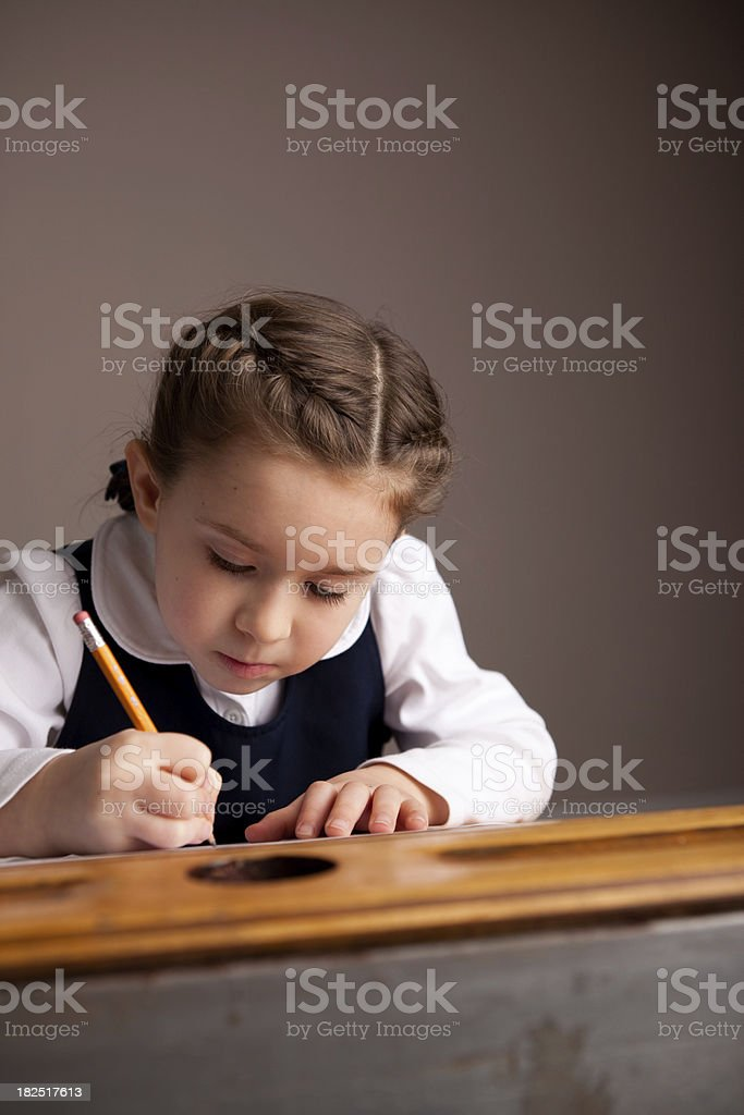 Young Girl Student Writing While Sitting in School Desk royalty-free stock photo