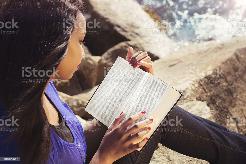 Young Girl Studying Her Bible Outdoors stock photo