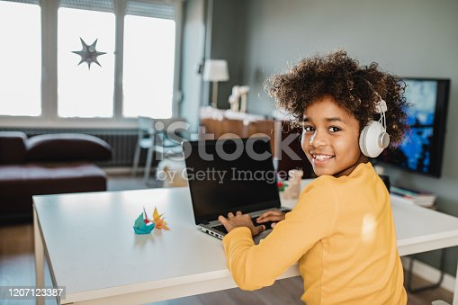 Young African american girl at home sitting on the table, using laptop, studying and looking at camera